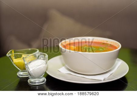 Close up bowl with borscht and two sauceboats on restaurant table