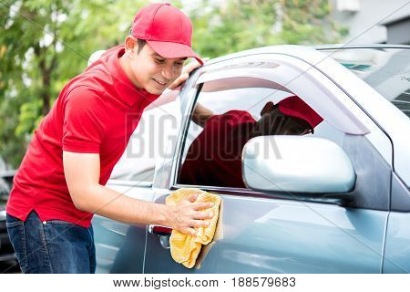 A man in red uniform cleaning car - auto service concept