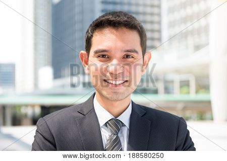 Smiling friendly Asian businessman in blur building background