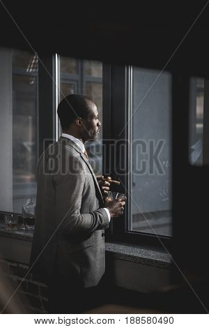 Pensive African American Businessman In Suit With Glass Of Whiskey Smoking Cigar