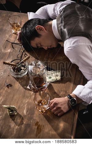 side view of drunk businessman sleeping at table after party