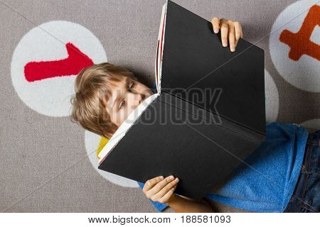 Little boy reading book on the floor at home
