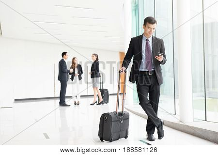 Business people (flight attendants) with luggage in building hallway (airport terminal)