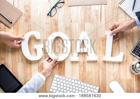 Business people hands arranging letters GOAL on working table -goal setting concept