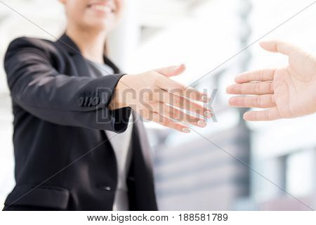 Businesswoman going to make handshake with a businessman -greeting dealing merger and acquisition concepts