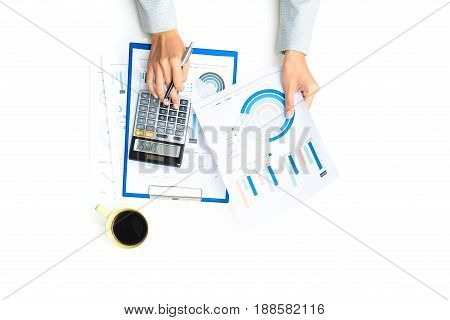 Top view of woman hands calculating and working with financial graph documents on white table - data analysis concept