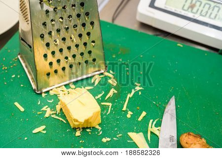 Close up piece of grated cheese with grater and knife on green plastic board
