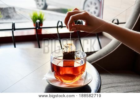 Closeup female hand puts teabag put in water in teacup on saucer