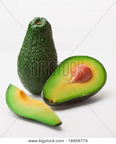 Two avocado, one sliced on half, another in one piece, isolated on a white background.