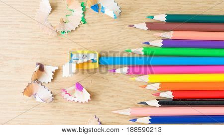 The Colorful Color Pencils With Sharpener And Shavings On The Wood Table.
