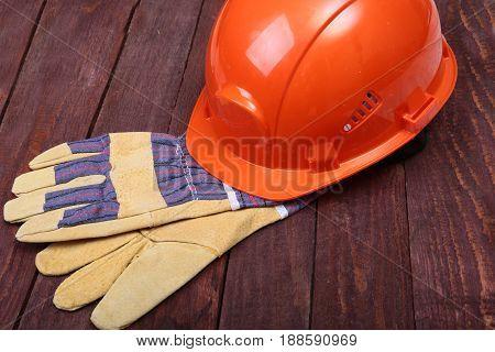 Orange hard hat and gloves for work on wood background