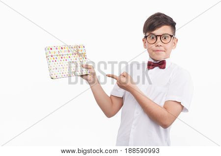 Boy in shirt and glasses holding giftbox in hands and pointing at it on white background.