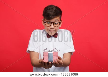 Impatient boy in glasses holding small giftbox on red background.