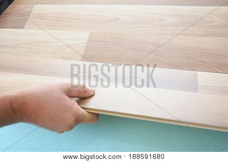 Contractor installing wooden laminate flooring with insulation and soundproofing sheets. Man laying laminate flooring. Man laying laminate flooring. Step by Step.