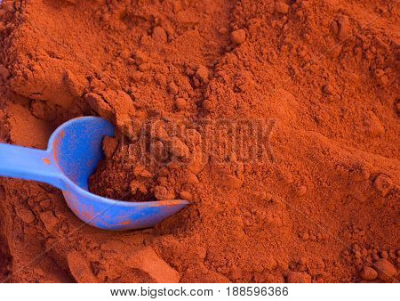 Close up of plastic scoop in red hot cayenne pepper pile