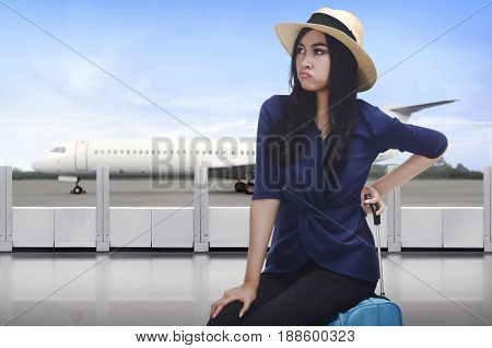 Portrait of asian traveler woman with unhappy face sitting on suitcase in the airport