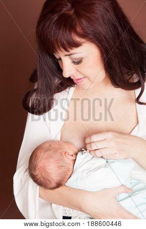mom feeding babe the son of breast milk to newborn