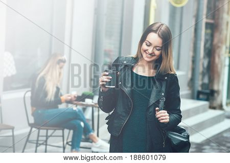 Take away coffee. Beautiful young urban woman wearing in black stylish clothes holding coffee cup and smiling while walking along the street. Student's coffee break after study. Fashion lifestyle.