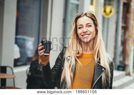 Coffee on the go. Beautiful young blonde woman holding coffee cup and smiling while walking along the street. The weather is great for walk and enjoy life. Fashion lifestyle outdoor concept.