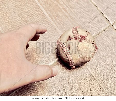 Hand Picking Up Aged and Torn Baseball. Baseball Is A One of Most Popular Sport in The World.