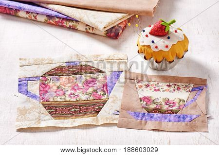 Patchwork blocks of the cup and the teapot with a pattern of flowers and the pin cushion like a cupcake with strawberry