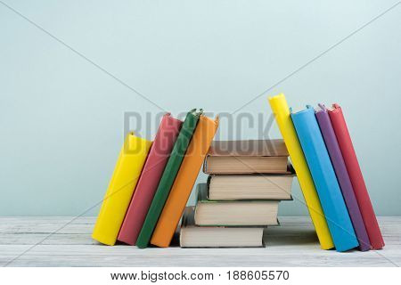 Book stacking. Open book, hardback books on wooden table and blue background. Back to school. Copy space for text