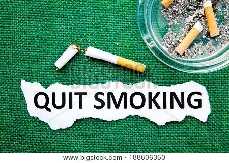 Quit Smoking - with ashtray, broken cigarette and printed text on green burlap background