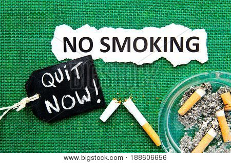 No Smoking - with ashtray, broken cigarette, handwritten blackboard and printed text on green burlap background