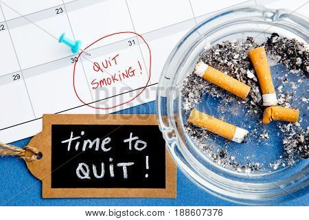 Quit Smoking - Calendar - Time to Quit - with ashtray and handwritten blackboard on blue background