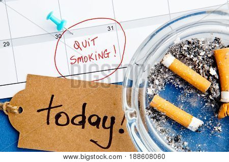 Quit Smoking - Calendar - Today - with ashtray and handwritten tag on blue background