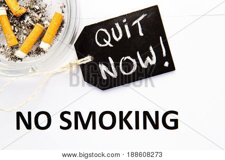 No Smoking - Quit Now - with cigarettes, ashtray and handwritten blackboard on blue background