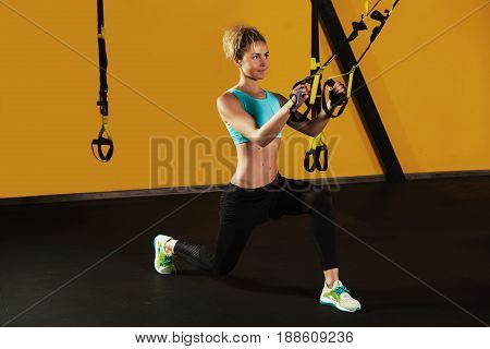 Sporty woman training her legs with suspension strap equipment, at modern gym. Workout for strong legs