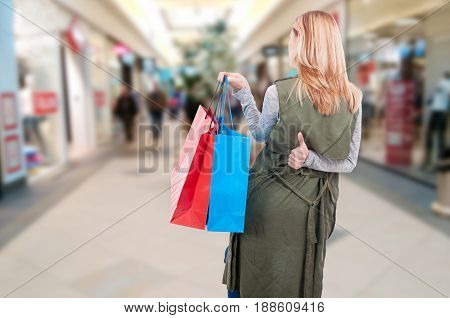 Rear View Of Woman With Shopping Bags Walking