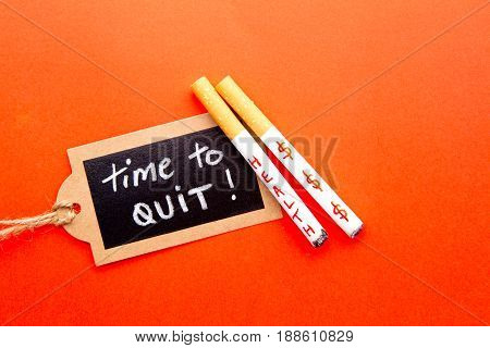 Quit Smoking - Time to Quit - with cigarettes and blackboard on red background