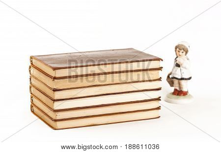 A pile of books and a porcelain keepsake on white background. Isolated.