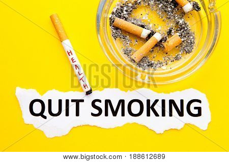 Quit Smoking - Health - with cigarettes, ashtray and printed text on yellow background