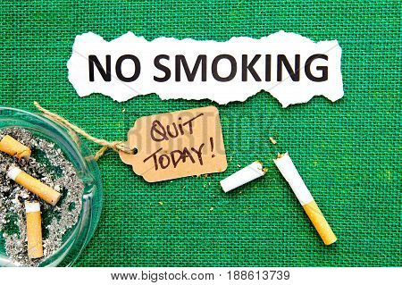 No Smoking - with ashtray, broken cigarette, handwritten tag and printed text on green burlap background