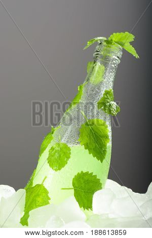A Bottle Of Lemonade With Mint On Ice