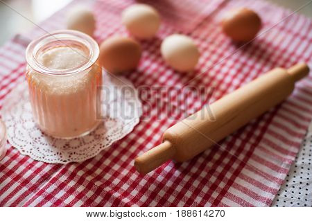 small children wooden rolling-pin sugar bowl and eggs on red and white checkerboard cloth