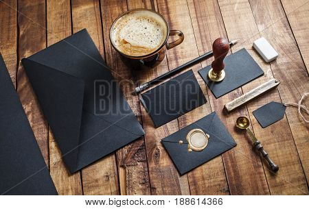 Set of black stationery elements on vintage wood table background. Branding template Photo of blank stationery. Mock-up for your design.