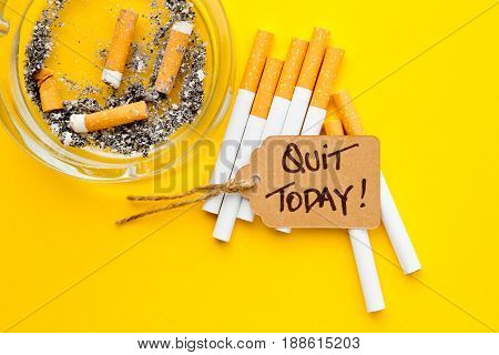 No Smoking - Time to Quit - with cigarettes, ashtray and handwritten tag on yellow background