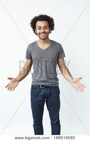 Stylish and handsome african man with arms wide open against white wall inviting to a gig. Concert concept.