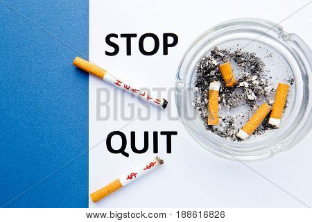 Stop Smoking - Stop and Quit - with cigarettes and ashtray with printed words on blue and white background