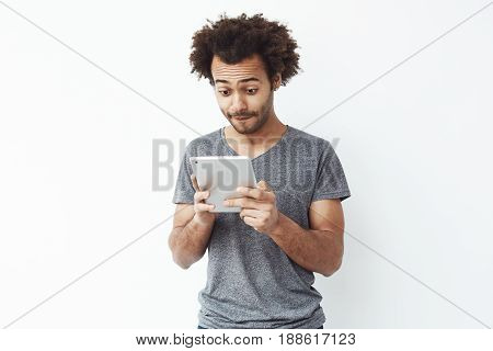 Interested handsome african man looking at tablet over white bakground. Copy space.