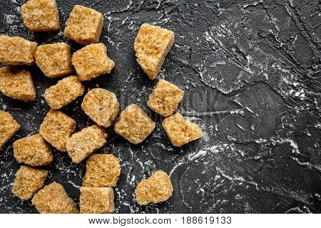brown sugar in lumps for sweet food cooking on kitchen dark table background top view mock up