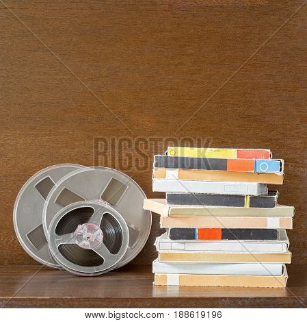 Vintage magnetic audio tapes, reel to reel type, paper box on the grunge wooden shelf