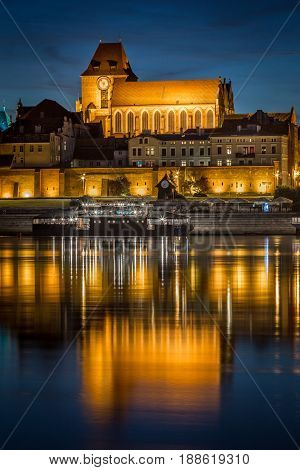 StJohn's Baptist and St John's Evangelist cathedral reflected in Vistula river at calm evening Torun Poland