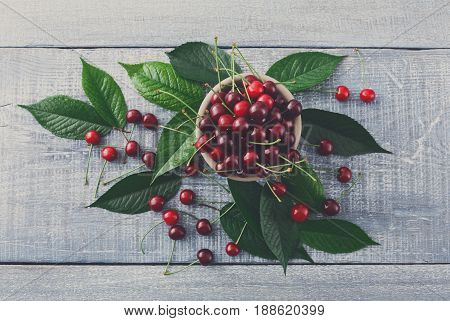 Sweet fresh cherries in a bowl with green leaves on blue rustic wood, fruit backround. Healthy food top view