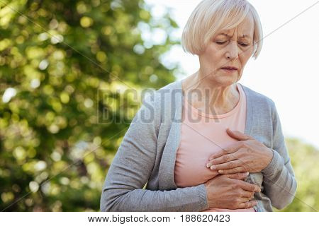 Problems with my heart . Retired helpless ill woman touching her chest and expressing disturbance while having heart attack in the park