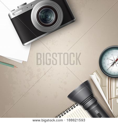 Vector compact photo camera with blank piece of paper, notepad, pencil, compass, map, flashlight and place for copyspace top view on table